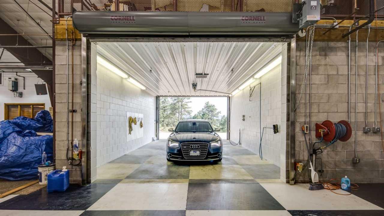 Audi sedan sitting in a custom built car wash with checkered floor.