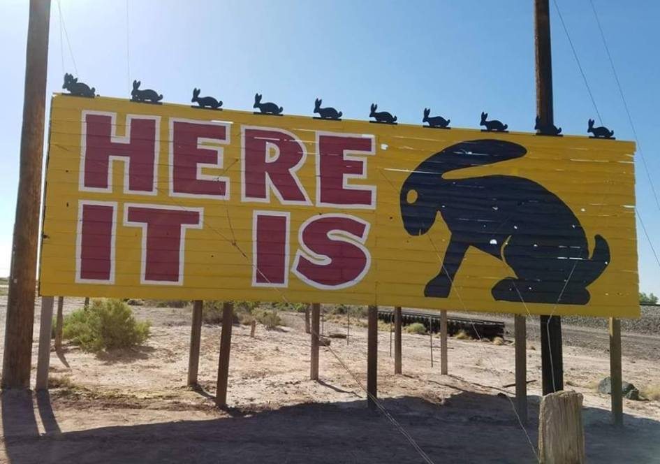 """<img src=""""cars-sign.jpg"""" alt=""""'Here It Is' Sign and Jack Rabbit Trading Post"""">"""